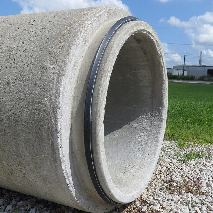 Concrete pipe sitting in gravel near grass